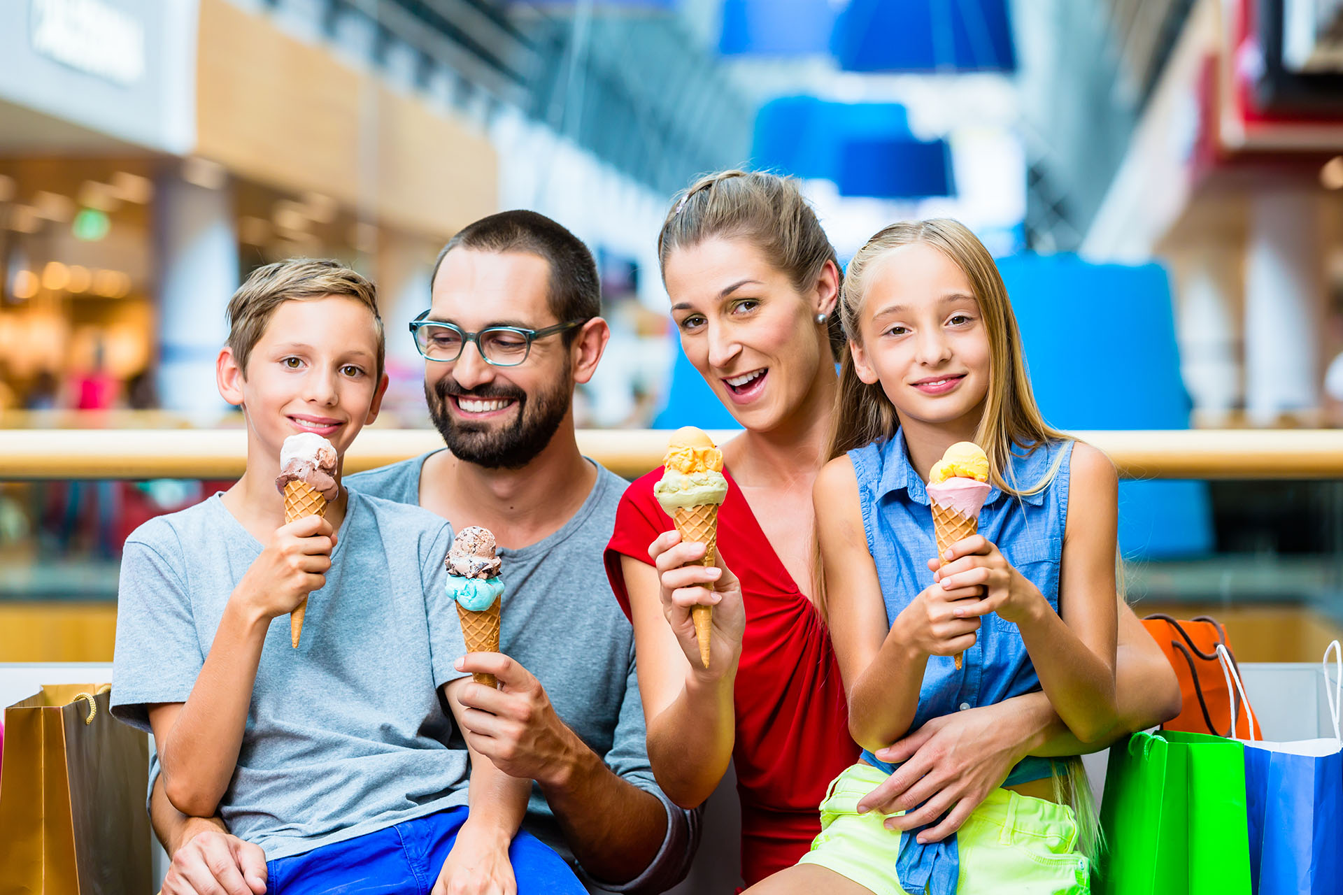 Family enjoying ice cream cones in public